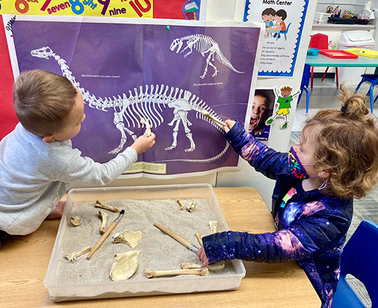 Two small children matching bones with against the image of a dinosaur skeleton