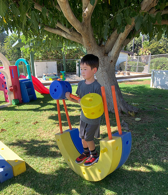 Youg Boy Under A Tree Playing With Giant Tinker Toys