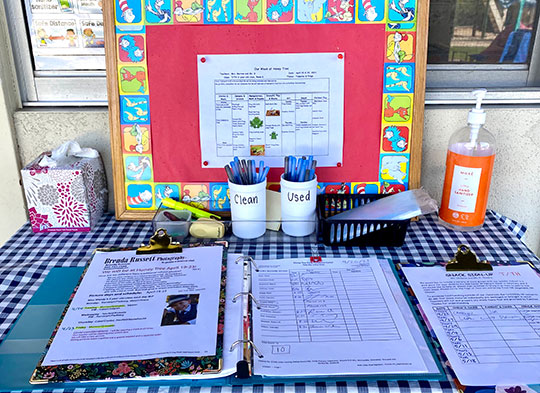 Sigin In Table with A Bulletin Board With The Weekly Schedule