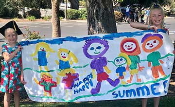 Two Children Hold Up Happy Summer Sign