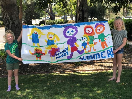 Two children holding a Happy Summer Hand Painted Sign