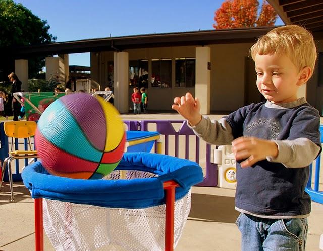 Small boy shooting a basketball into a basket.
