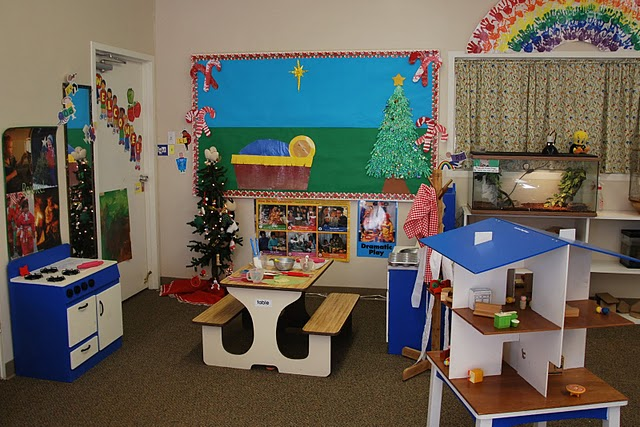 Colorful classroom with play stove, picnic table, doll house and more.