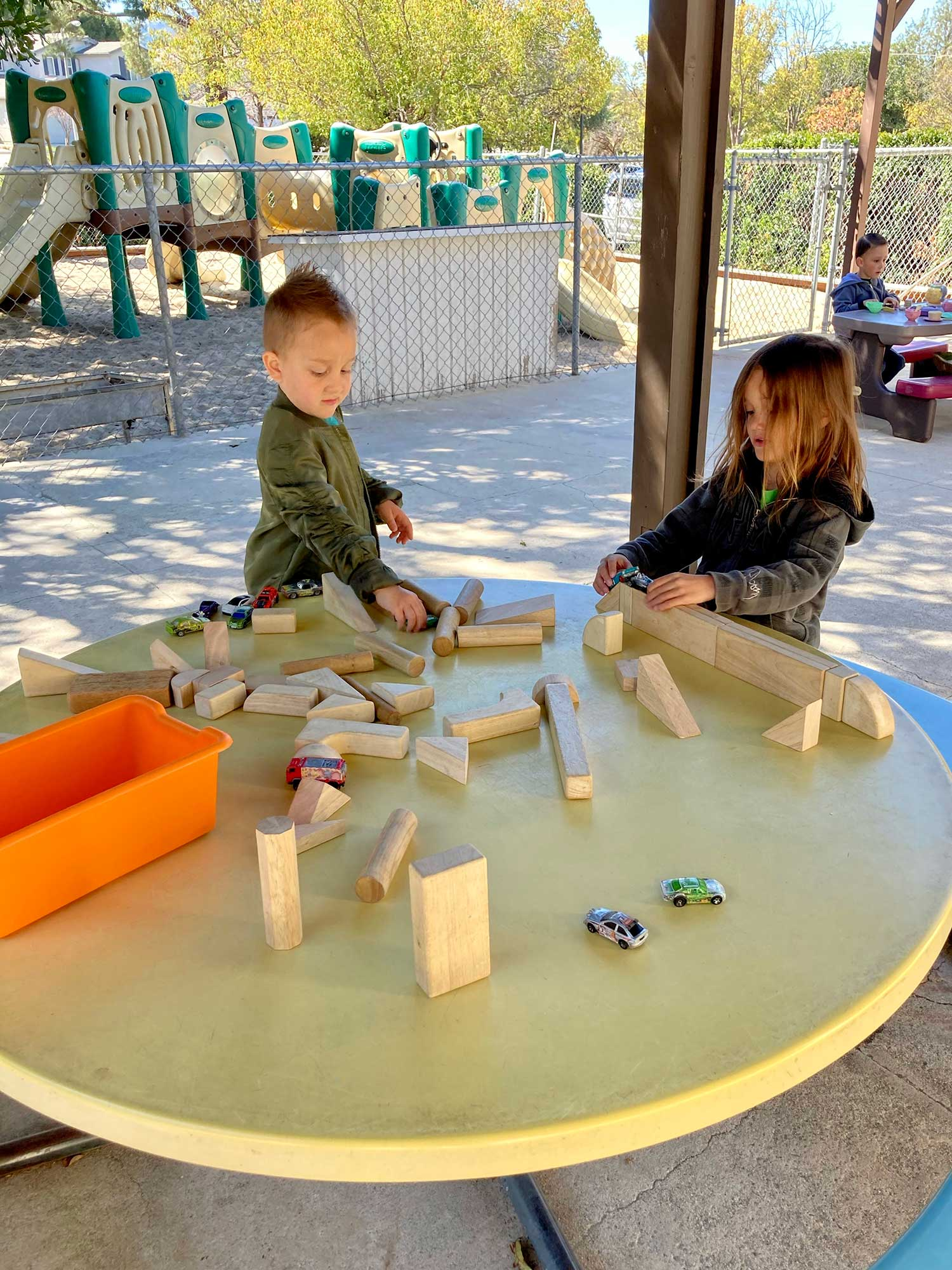 Girl and Boy Playing with Blocks and Cars on Outdoor Table