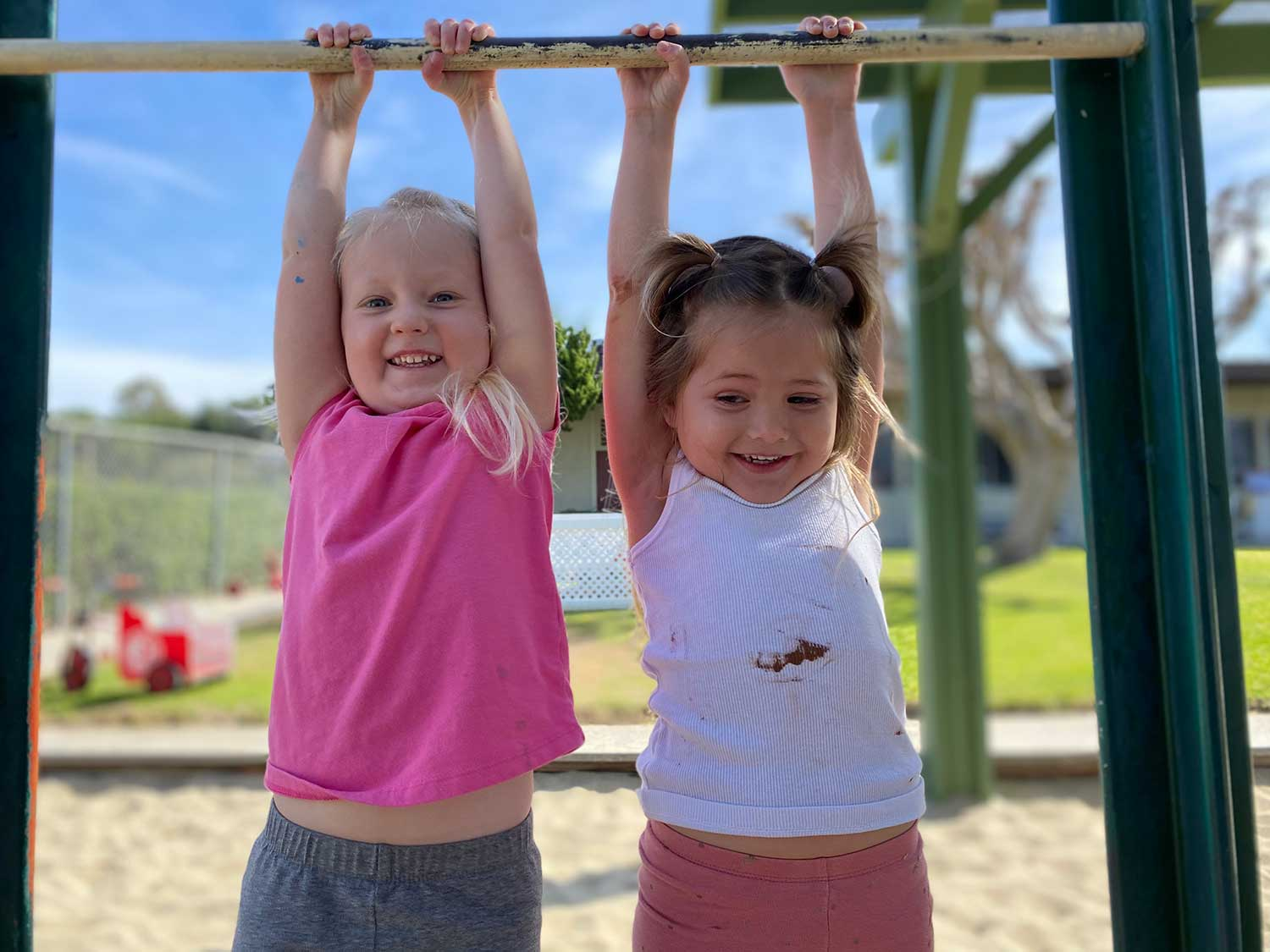 Two Girls Hanging From Jungle Gym