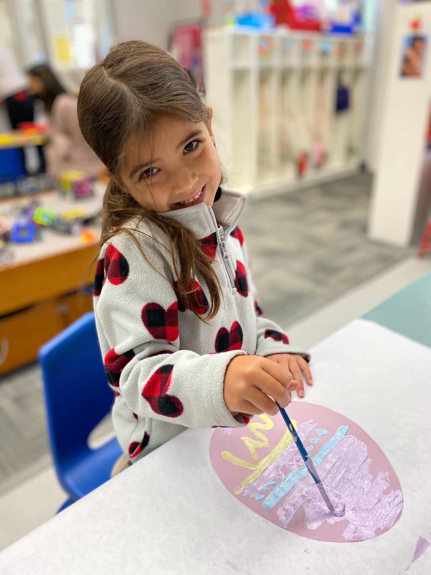 Smiling Girl Painting a Paper Easter Egg