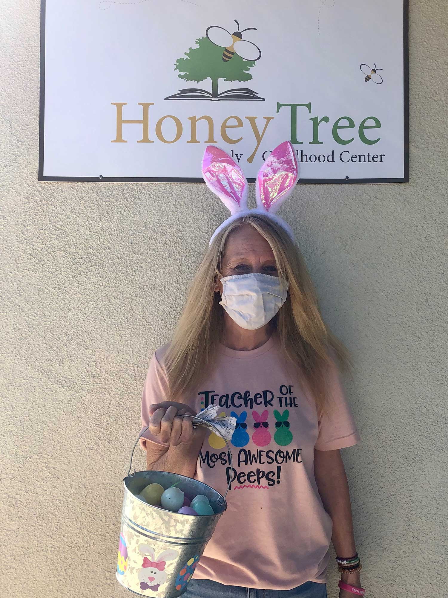 Teacher with Rabbit Ears In Front of Honey Tree Sign
