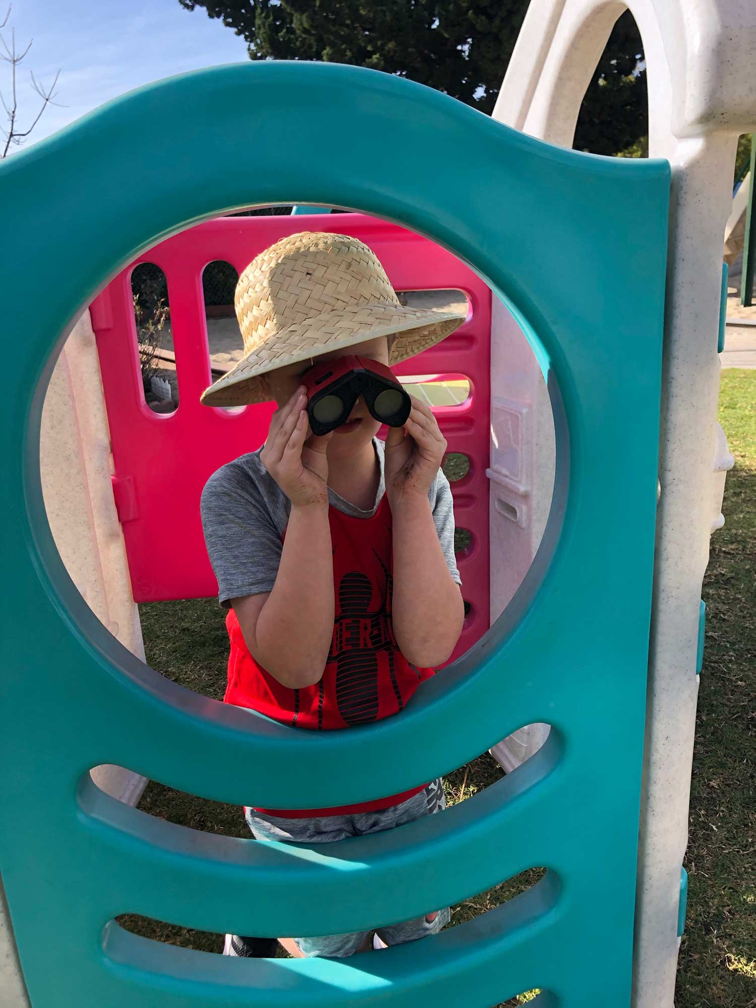 Child With Binoculars and Straw Hat